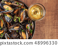 Skillet of marinara mussels on rustic background with wine and place for text 48996330