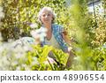 Senior woman working in her garden 48996554