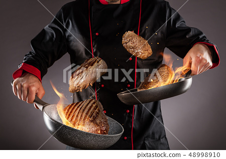 Closeup of chef throwing beef steaks into the air 48998910