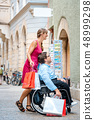 Woman and man in wheelchair with shopping bags 48999298