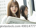 Two women reading a newspaper on the window side 49014777