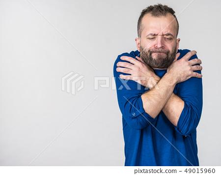 Man feeling cold gesturing 49015960