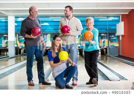 Family holding colorful bowling ball 49018385