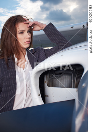 Businesswoman standing by his private plane 49020598