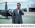 Businessman talking on cellphone near private helicopter 49020669