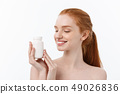 Portrait of good-looking young caucasian woman holding pills, trying to take care of immune system 49026836
