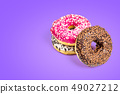 Sweet donuts isolated on violet background 49027212