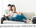 Relaxed couple using a generic mobile phone together sitting on a sofa in the living room at home 49029470