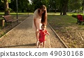 child learns to walk along path in park in summer, mother walks with the baby 49030168