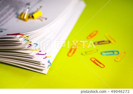 책상위에 놓여진 다양한 색상의 클립이 끼워진 서류들. 49046272