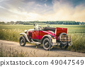 Antique red car on a road in a countryside 49047549