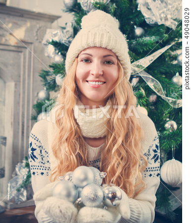 Young blond woman holding silver decorative balls 49048029