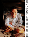 Serious professional baker standing near table after making bread 49050736