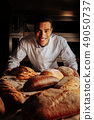 Baker smiling broadly standing near table with bread 49050737