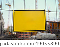 Blank sign hanging on fence at construction site - 49055890