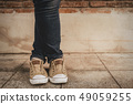 Shapely female cross one's legs  in sneakers and 49059255