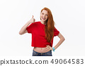 Happy young caucasian female making thumb up sign and smiling cheerfully, showing her support and 49064583