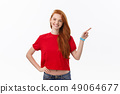 Photo of happy young woman standing isolated over white wall background. Looking camera showing 49064677