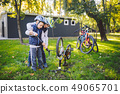 Two children, older boys and younger brother learning repair bike. Two guys siblings in helmets and 49065701