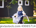 Funny child Caucasian girl blonde near a purple bike with a basket and a zebra toy in an outside 49065714