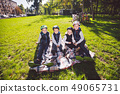 large family Caucasian children. Three brothers and sister sitting resting on blanket outside the 49065731