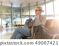 Female traveler talking on her cell phone while waiting to board a plane at departure gates at 49067421