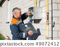 specialist man repairs a gas meter hanging 49072412