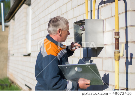 specialist man repairs a gas meter hanging 49072416