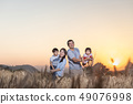 Family having fun and playing in a wheat field in 49076998