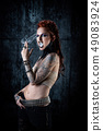 Young tattooed woman, one-eyed, a cigarette in her 49083924