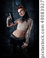 Young tattooed woman, one-eyed, bottle in hand 49083927