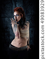 Young tattooed woman, one-eyed, finger to mouth 49083929