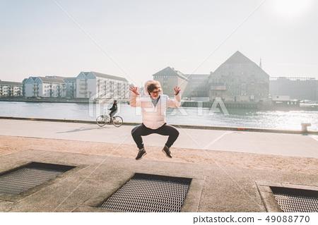adult person rejoices like child. Playground trampoline in ground, children trampoline, springs 49088770