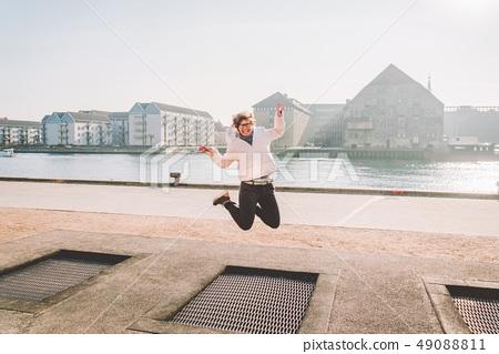 adult person rejoices like child. Playground trampoline in ground, children trampoline, springs 49088811
