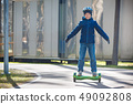Happy boy riding on self-balancing deck in city park 49092808