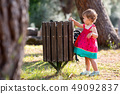 Sweet blond little baby girl throwing garbage into recycle bin 49092837