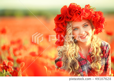 Portrait of a girl on the street with a wreath of poppy flowers on the head 49107628