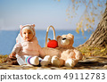 Child autumn sitting on the shore of the blue sea on a picnic 49112783