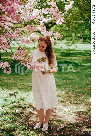 beautiful cute brunette girl bride in cream lace dress, with decoration on the hair, near the tree 49114272