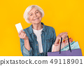 Senior woman shopper studio isolated on yellow wall with bags and credit card 49118901