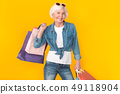 Senior woman shopper studio isolated on yellow wall wearing sunglasses carry bags 49118904