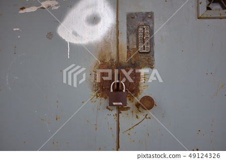 Brown lock on rusty grey iron door 49124326