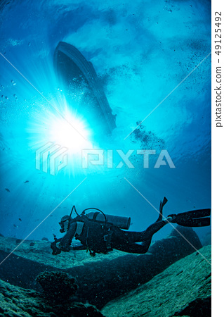 boat ship from underwater blue ocean with sun rays 49125492