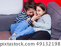 Brother and sister playing on bed 49132198