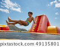Boy playing on water trampoline on the sea at sunny day 49135801