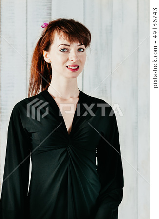 pretty smiling woman in black dress light backdrop 49136743