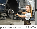 Pretty girl working as mechanic in autoservice, fixing car. 49140257