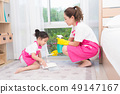 mother teaching daughter cleaning their home 49147167