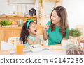 mother and daughter having breakfast together  49147286