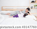 Pregnant mother breast feeding daughter on bed  49147760